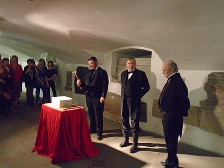 Stejní herci v rolích Sladkovského, Palackého a Purkyně poklepávají na základní kámen zlaté kapličky